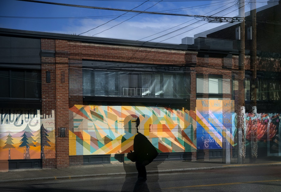 caption: A jogger reflected in the window of a closed business runs along Ballard Avenue in front of painted murals on Sunday, May 3, 2020, near the intersection of 20th Avenue Northwest in Seattle. The murals, from left, were painted by artists Carolyn Wassmer, Sean Mullin and Gynn Rosenberg.