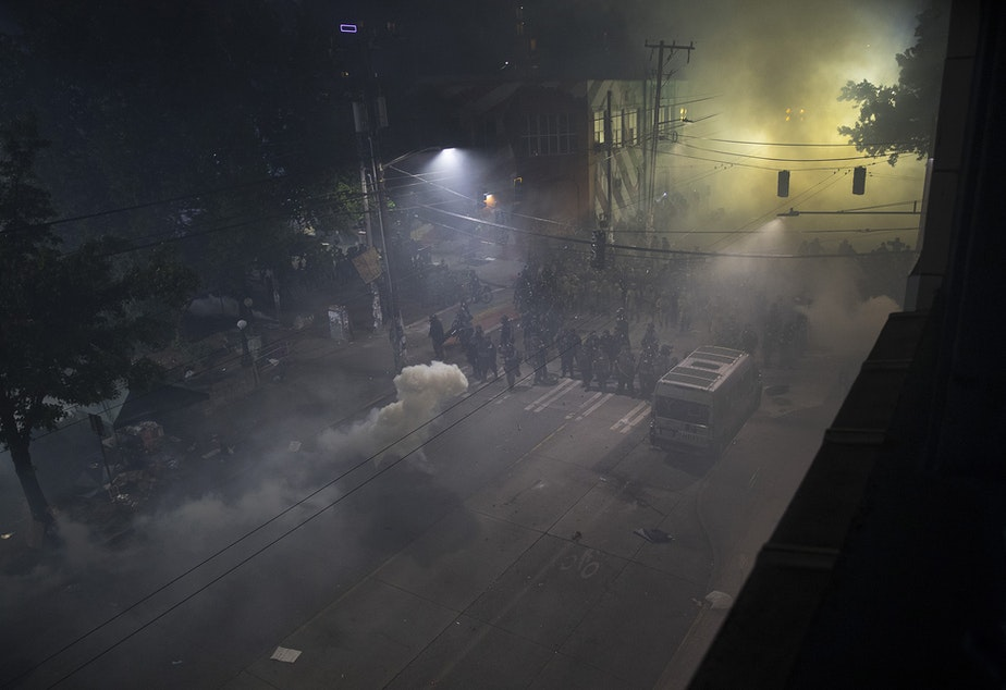 caption: Seattle police officers are shown shrouded in tear gas at the intersection of East Pine Street and 11th Avenue at 12:12 a.m. on Monday, June 8, 2020, in Seattle.