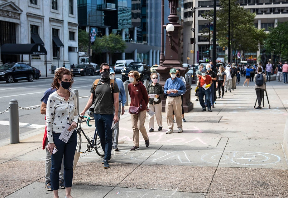 caption: People wait in line to cast their vote during early voting at City Hall in Philadelphia on Oct. 7.