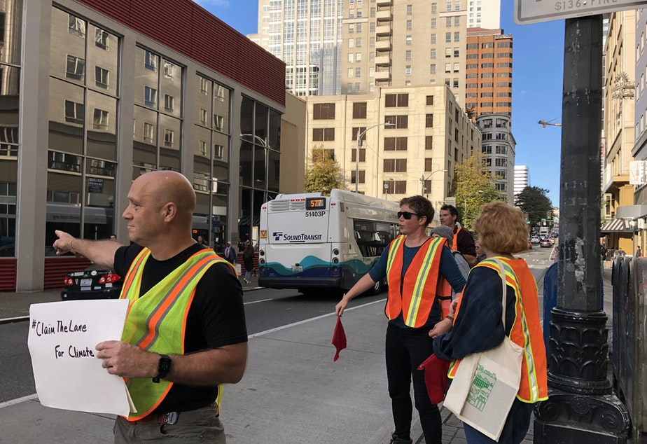 caption: Climate activists shoo car drivers out of a bus-only lane in downtown Seattle in September 2019.