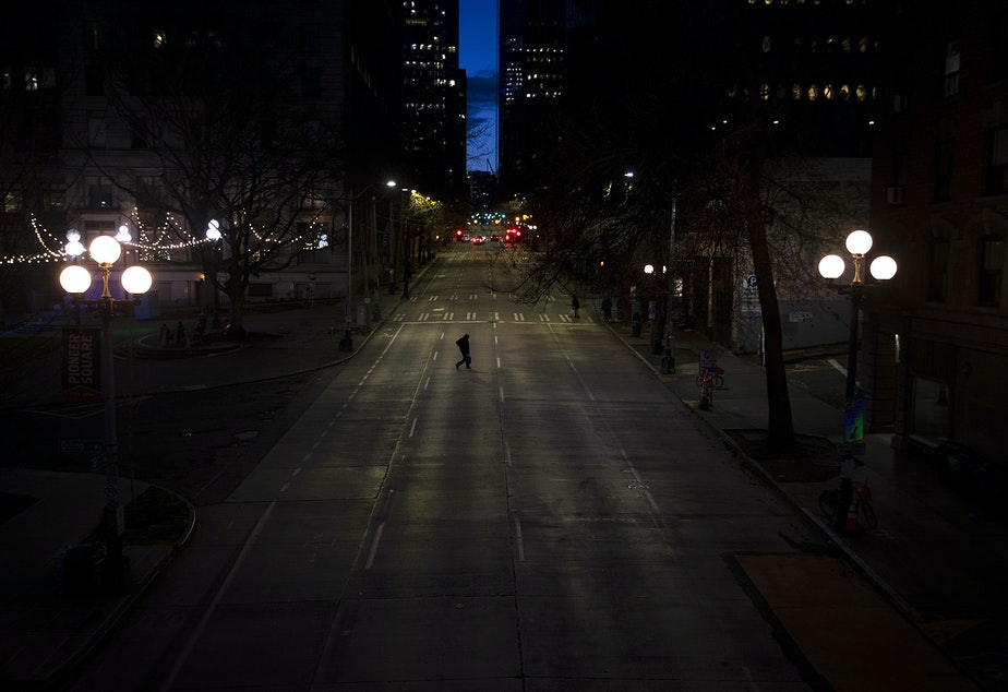 caption: A pedestrian crosses an empty 4th Avenue on Wednesday, March 25, 2020, in Seattle. On March 23, Gov. Jay Inslee announced he would sign a statewide order that requires everyone in the state to stay home in order to curb the spread of the virus. At the time, the Stay Home, Stay Healthy order was to last for two weeks and could be extended.