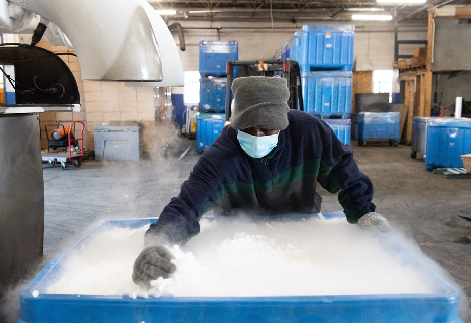 caption: An employee makes dry ice pellets at Capitol Carbonic, a dry ice factory in Baltimore in Nov. 2020. Dry ice helps keep COVID-19 vaccines cool during transport.