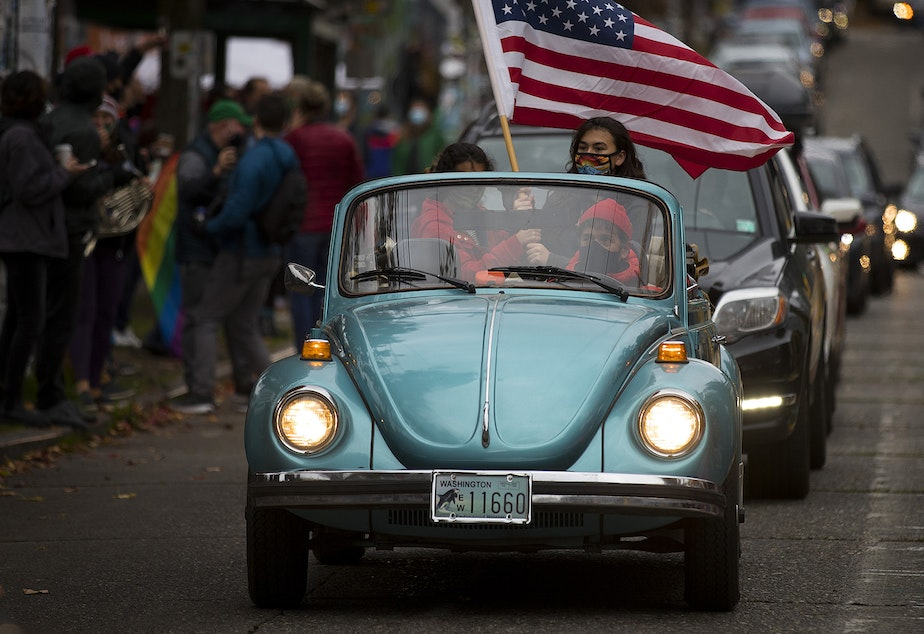 caption: Joshua Trujillo drives as his daughters, Ravenna, 14, and Araya, 12, wave an American flag to celebrate the first female Vice President in America during an impromptu car parade and celebration after the results of the 2020 presidential election were made official on Saturday, November 7, 2020, near the intersection of 10th Avenue and East Pine Street in Seattle.