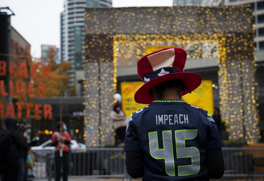 caption: Teri McClain waits for the start of the Our Work Continues: Protect Every Person event, shortly after Joe Biden was officially named the president elect on Saturday, November 7, 2020, at Westlake Park in Seattle.