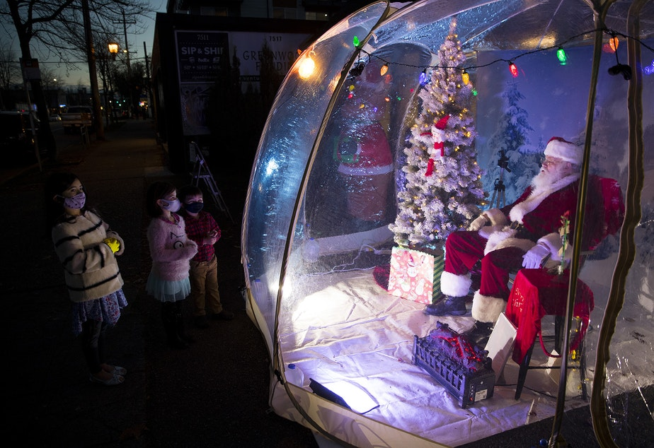caption: From left, Jasper, 7, Paloma, 6, and Otto, 4, talk with The Seattle Santa, Dan Kemmis, on Sunday, December 6, 2020, as he sits inside of a pandemic safe snow globe at the intersection of Greenwood Avenue North and North 76th Street in Seattle.