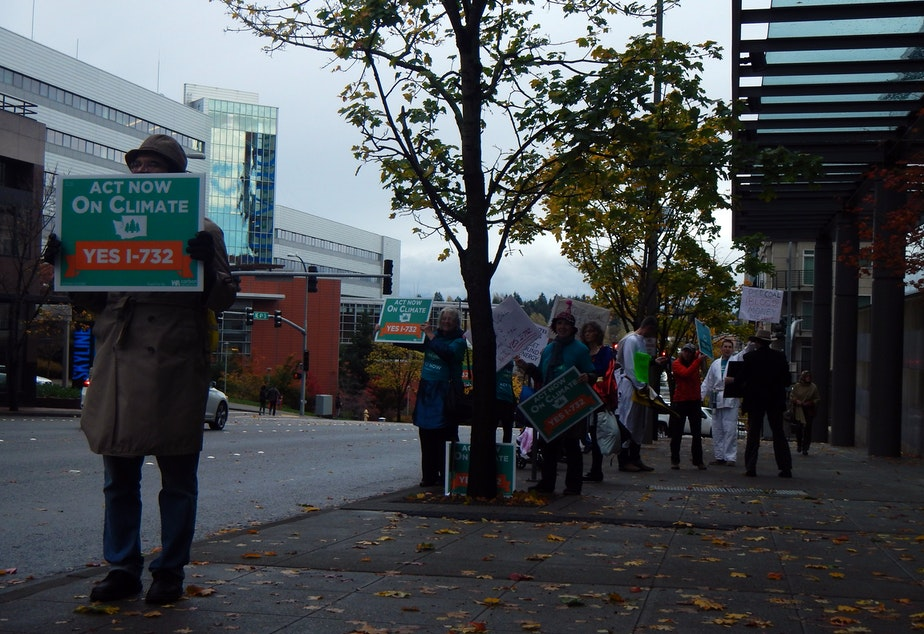 caption: Supporters of a carbon tax demonstrate outside Puget Sound Energy headquarters in Bellevue, Washington.