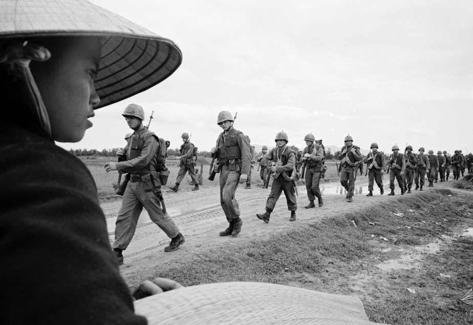 caption: Marines marching in Danang. March 15, 1965.