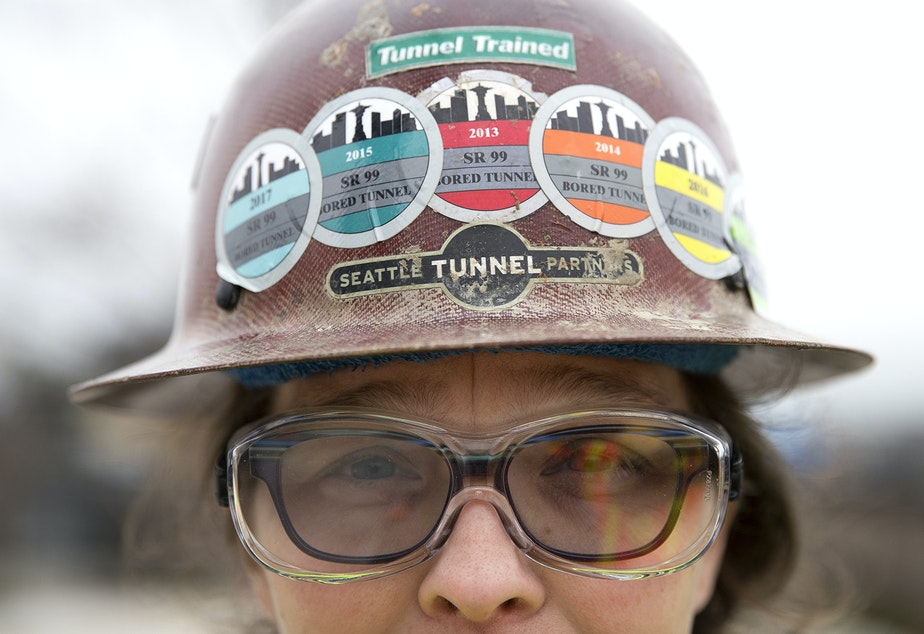 caption: Safety representative for the Seattle Tunnel Partners, Marisa Roddick, wears stickers on her helmet for each year that she has worked on the tunnel project, from 2013 to 2018, on Tuesday, March 27, 2018, in Seattle.
