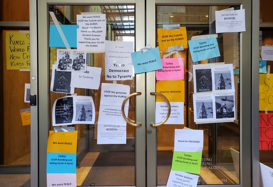 caption: Kurdish protesters taped signs to the front door and windows of the Commercial Attache of Turkey on Sunday, October 13th, 2019.