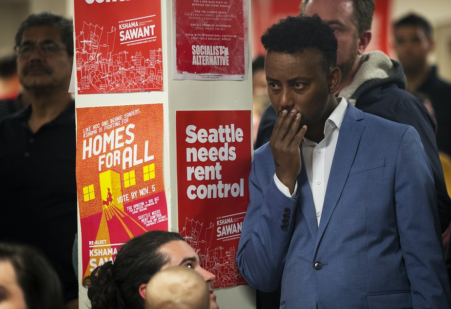 caption: Hassan Diis reacts as early election results show councilmember Kshama Sawant trailing behind her District 3 opponent Egan Orion on Tuesday, November 5, 2019, during an election night party at Langston Hughes Performing Arts Institute in Seattle.