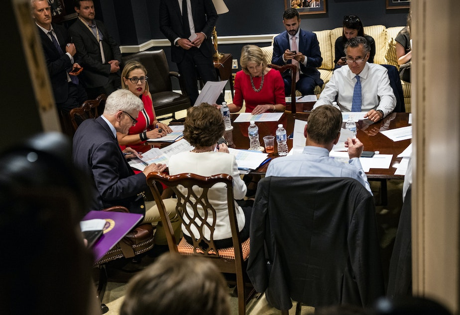 caption: From left: Sens. Bill Cassidy, R-La., Kyrsten Sinema, D-Ariz., Lisa Murkowski, R-Alaska, Mitt Romney, R-Utah, and others hold a bipartisan meeting on infrastructure in the basement of the U.S. Capitol on Tuesday.