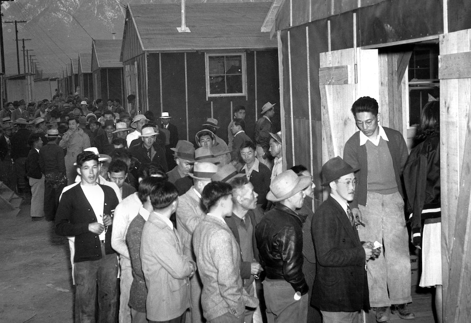 caption: People of Japanese descent wait in line for their assigned homes at an internment camp reception center in Manzanar, Calif., the same camp in which John Tateishi was detained as a child.