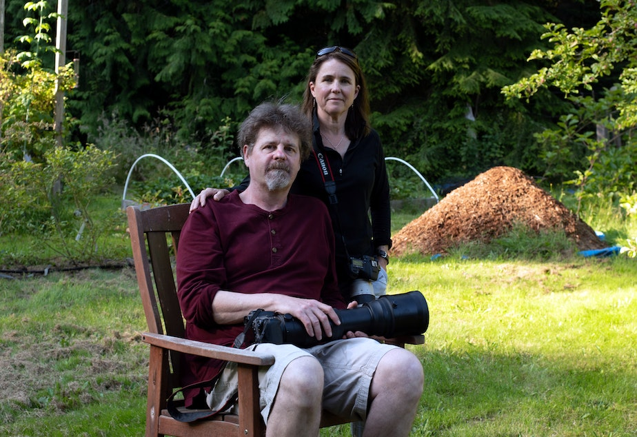 caption: Michelle and Dave Grimmer in their backyard on Marrowstone Island, Washington. They started the Facebook group Pacific Northwest Birding.