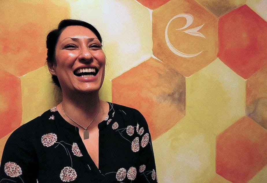 caption: Maryam Mirnateghi poses in front of her brand logo at the Canna West dispensary in West Seattle.