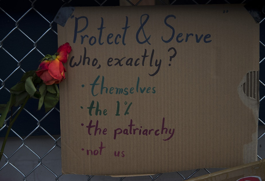 caption: Signs and flowers are secured to a fence outside of the Seattle Police Department's East Precinct building in the Capitol Hill Occupied Protest (CHOP) zone on Tuesday, June 16, 2020, in Seattle.