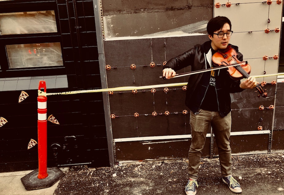 Joe Kye plays the violin on the Ave in the University District after his interview at KUOW.