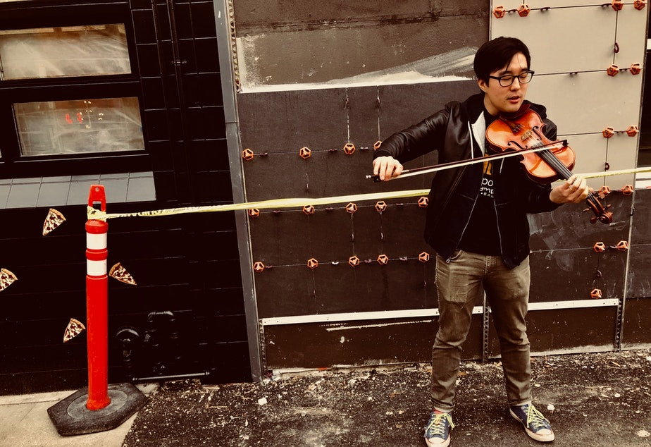 caption: Joe Kye plays the violin on the Ave in the University District after his interview at KUOW.