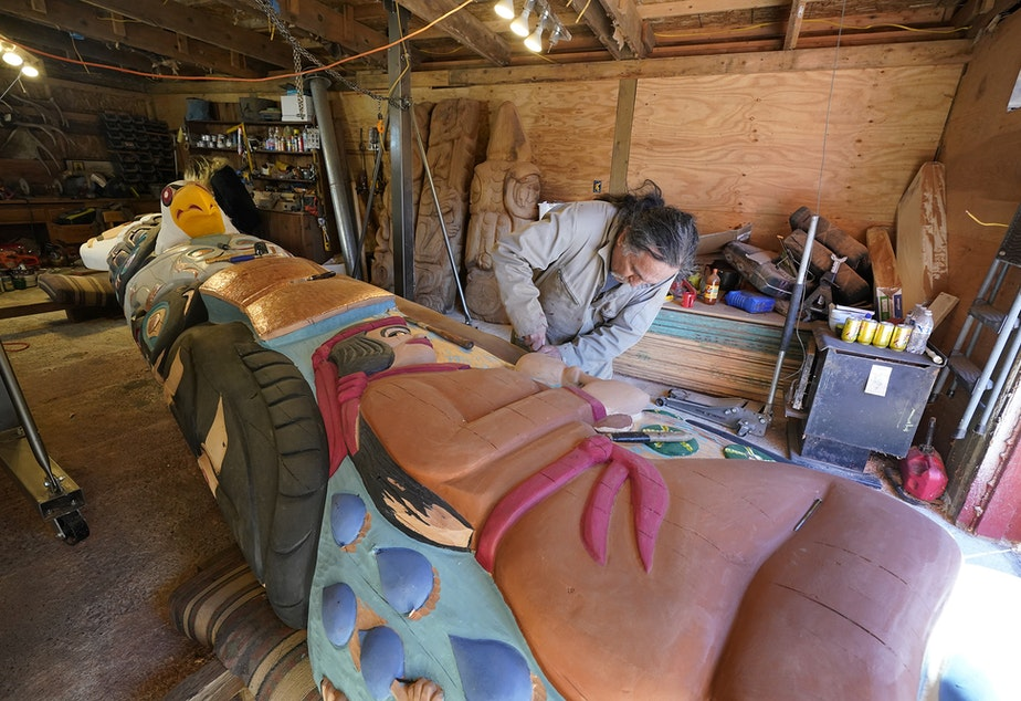 caption: Lummi Nation lead carver Jewell James works on the final details of a nearly 25-foot totem pole to be gifted to the Biden administration, Monday, April 12, 2021, on the Lummi Reservation, near Bellingham. The pole, carved from a 400-year old red cedar, will make a journey from the reservation past sacred Indigenous sites, before arriving in Washington, D.C. Organizers said that the totem pole is a reminder to leaders to honor the rights of Indigenous people and their sacred sites.