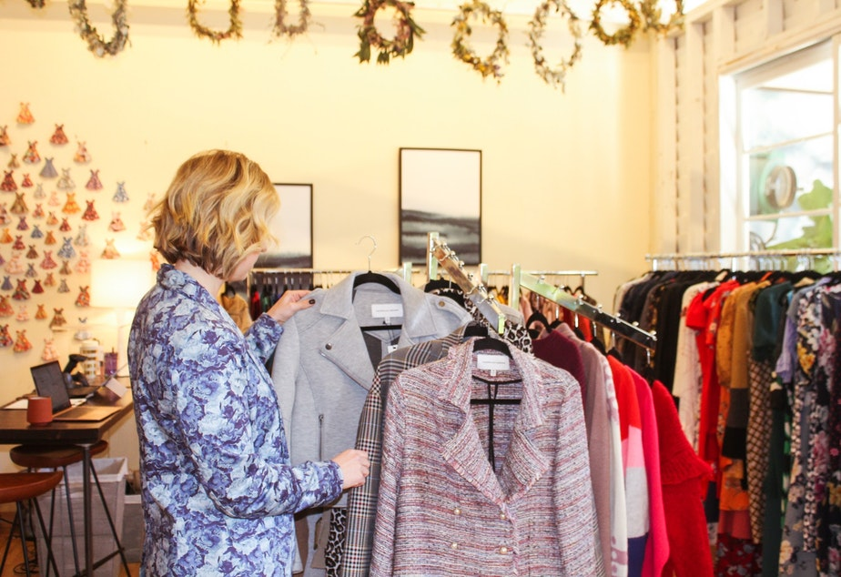 caption: A customer looks at jackets at Armoire.