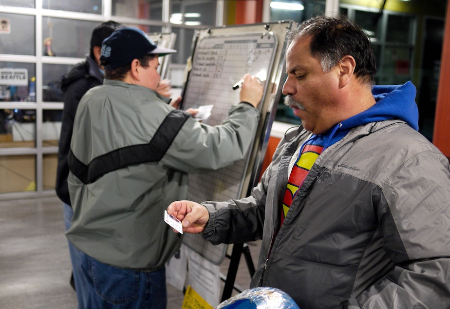 caption: Workers at Casa Latina run a morning lottery to distribute job requests for housecleaning, painting, yard work and other odd jobs.