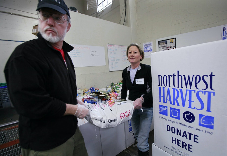 Volunteers Ken Newman, right, and Caren Shepsky heft a 50-pound bag of rice at the Cherry Street Food Bank, run by Northwest Harvest, Wednesday, Nov. 11, 2009, near downtown Seattle. Northwest Harvest, a non-profit hunger relief agency, also provides food for over 300 partner programs state-wide. American charities say they have weathered about a 9 percent drop in giving this year and a recent survey show they may see a decrease in year-end generosity.