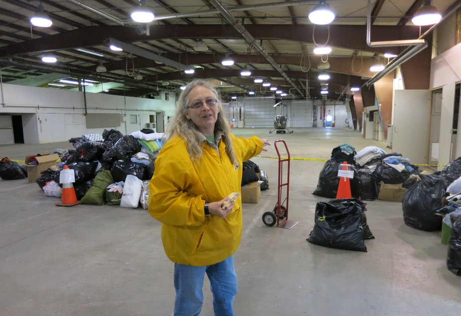 caption: Shirley Clark surveys the hangar at the Arlington airport where goods for Oso relief have been collected. With donations piling up, she has been walking about with a half-eaten sandwich and trying to keep organized.