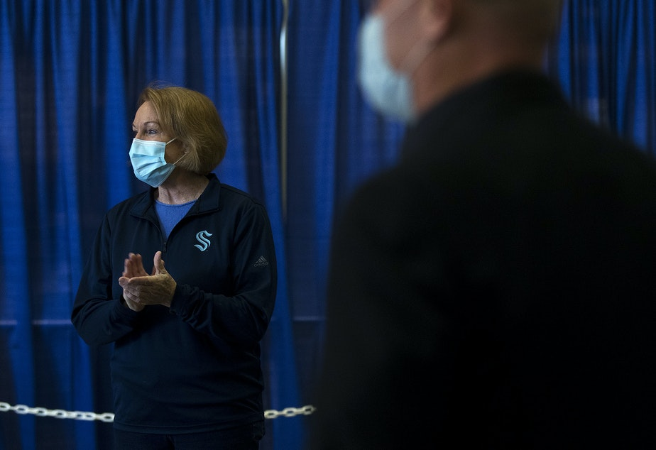 caption: Seattle mayor Jenny Durkan, left, claps as the first patients arrive to be vaccinated against Covid-19 at the new civilian-led mass vaccination site at Lumen Field Events Center on Saturday, March 13, 2021, in Seattle.