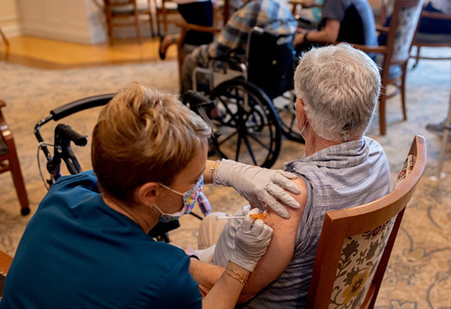 caption: A health care worker administered a third dose of the Pfizer-BioNTech Covid-19 vaccine at a senior living facility in Worcester, Penn., in August.