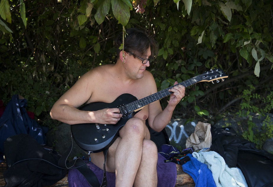 caption: Dan O'Day plays guitar on Monday, August 27, 2018, at Denny Blaine Park in Seattle.