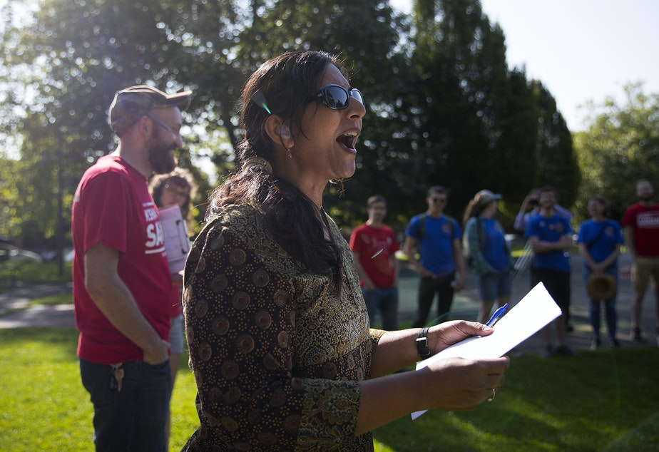 caption: Councilmember Kshama Sawant talks to a group of union members before they go door knocking on Sunday, August 4, 2019, at Pratt Park in Seattle.