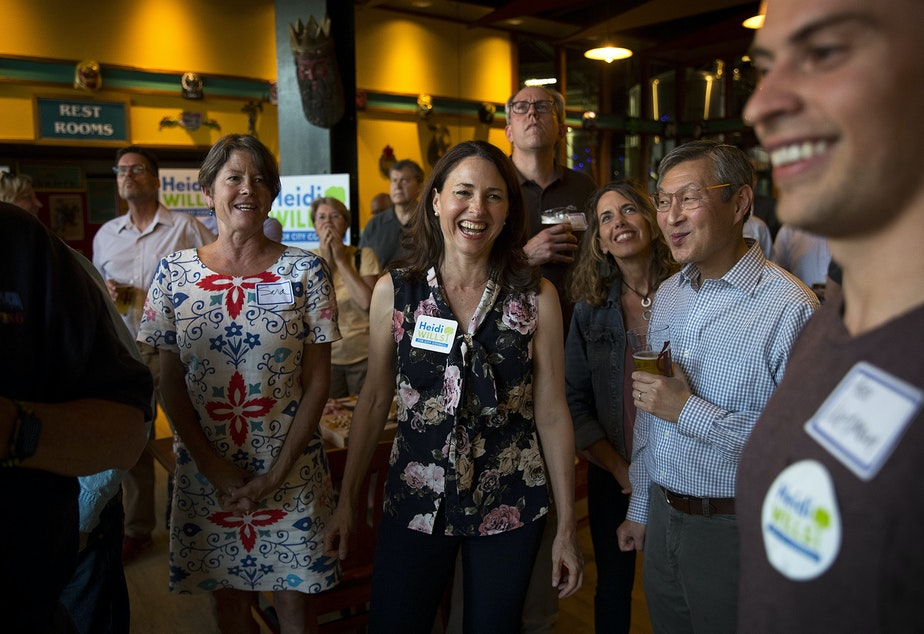 Seattle city council candidate in the 6th district Heidi Wills, center, smiles at her campaign manager, Alex Wenman, right, after the first election results came in on Tuesday, August 6, 2019, at Hales Ales in Seattle.