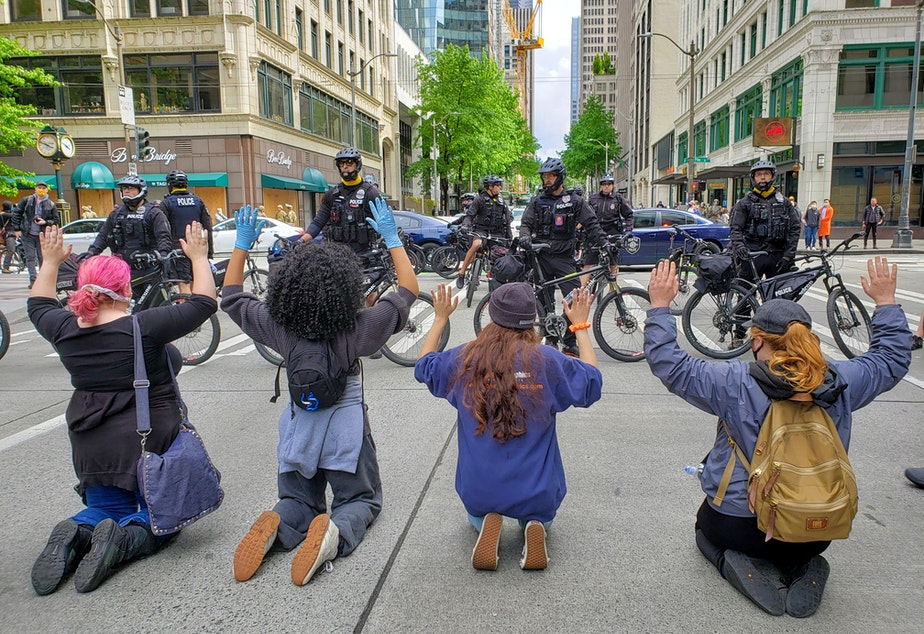 caption: Activists kneel in front Seattle Police during a protest on Sunday, May 31st, 2020.