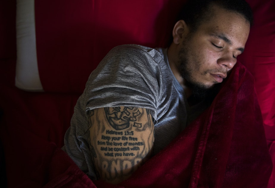caption: DaShawn Horne rests in his new bedroom on the first floor shortly after arriving home from spending 103 nights at Harborview Medical Center, on Thursday, May 3, 2018, at his home in Auburn.