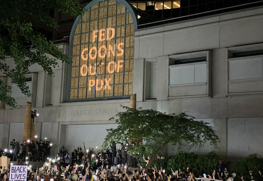 """caption: At the Multnomah County Justice Center in Portland, a projected image reads """"Fed Goons Out of PDX"""""""