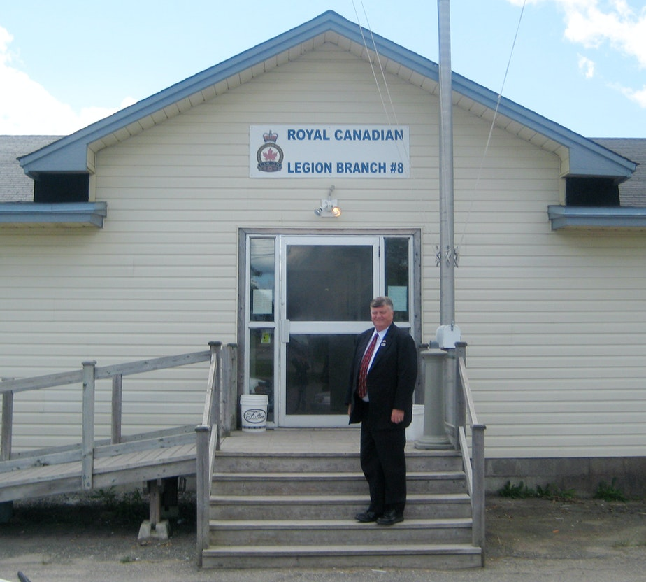 caption: Gander, Newfoundland, Canada Mayor Claude Elliott stands in front of the Royal Canadian Legion Hall, which was used as a shelter for passengers of a flight stranded on Sept. 11, 2001.