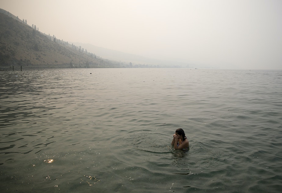 Bellaniy Baltazar, 13, rubs her eyes while swimming amidst heavy smoke from wildfires on Wednesday, August 15, 2018, at Lakeside Park in Chelan.