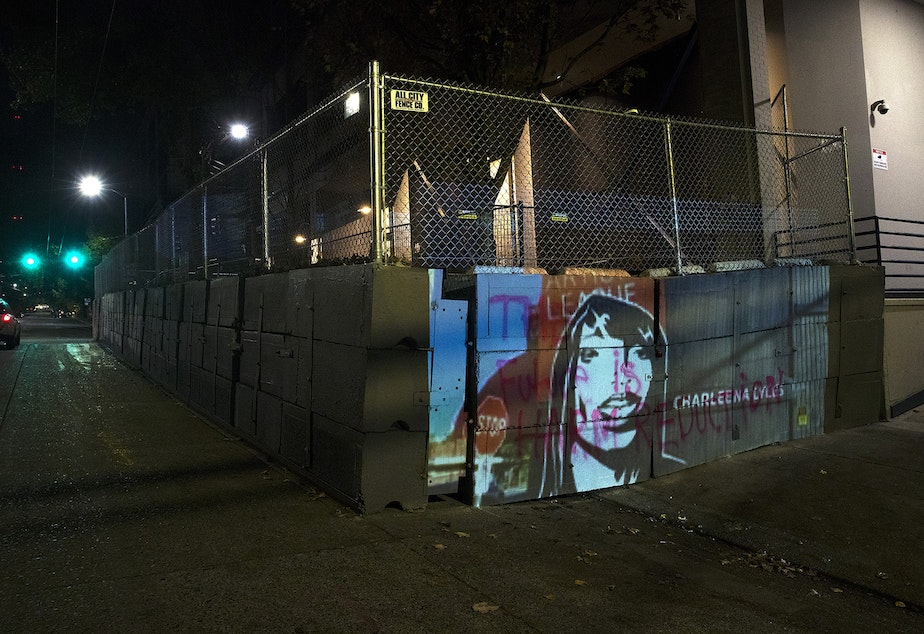 caption: An image of Charleena Lyles is projected onto the barricade surrounding the Seattle Police Department's East Precinct building on Monday, October 26, 2020, during the 150th day of protests for racial justice in Seattle. Lyles, a pregnant mother of four, was killed by Seattle Police Officers in 2017.