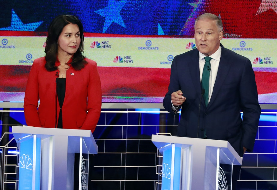 Democratic presidential candidates Washington Gov. Jay Inslee, right, speaks during a Democratic primary debate hosted by NBC News at the Adrienne Arsht Center for the Performing Art, Wednesday, June 26, 2019, in Miami, as Rep. Tulsi Gabbard, D-Hawaii, listens.