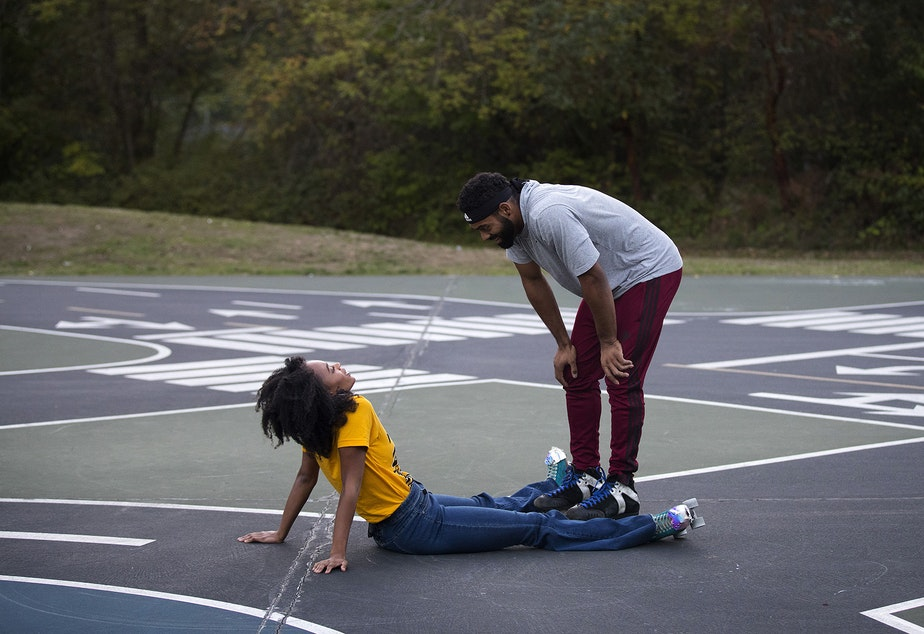 caption: JNiyah Williams, left, and Kayan Hanks, right, take a moment after JNiyah fell while skating together on Tuesday, October 6, 2020, at the Bicycle Playground in White Center.