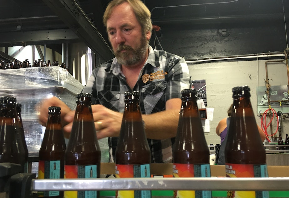 caption: Double Mountain Brewery founder Matt Swihart grabs freshly bottled pale ale from the bottling line in Hood River. The ale is among the first to be sold in Oregon's new refillable beer bottles.