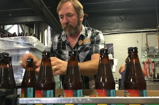 Double Mountain Brewery founder Matt Swihart grabs freshly bottled pale ale from the bottling line in Hood River. The ale is among the first to be sold in Oregon's new refillable beer bottles.
