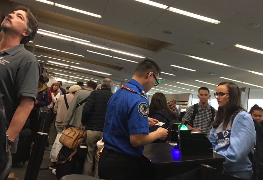 caption: Passengers in a security line at San Francisco International Airport.