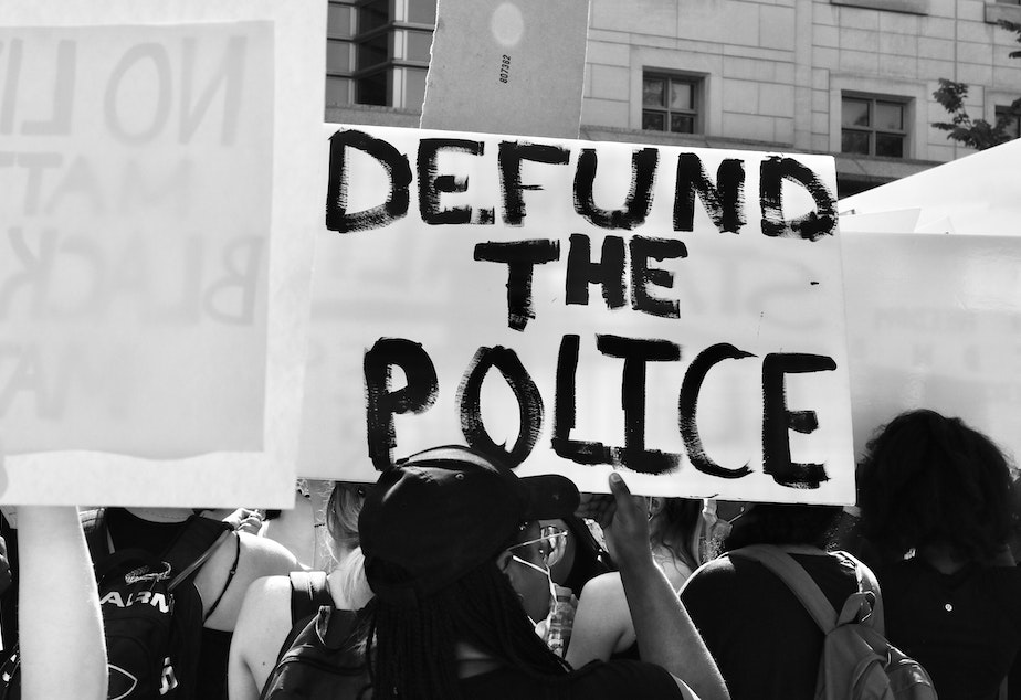 An anti-police brutality protester holds a sign that calls to defund the police