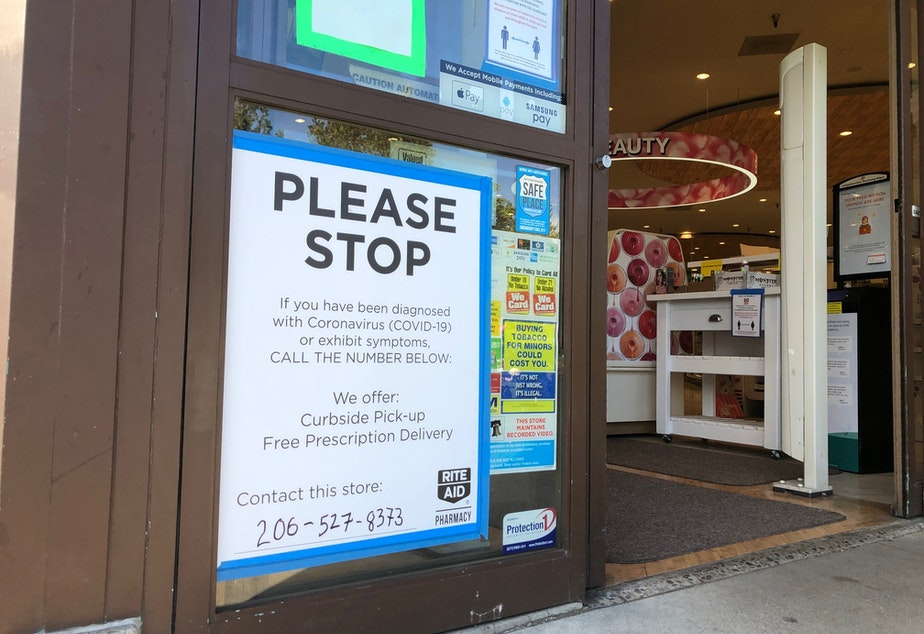 caption: The sign in front of a Seattle drug store attempting to mitigate contact with cases of Covid-19.