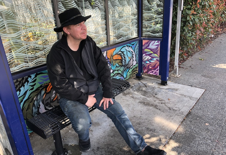 caption: Jay Michael Tunison at a bus stop in White Center