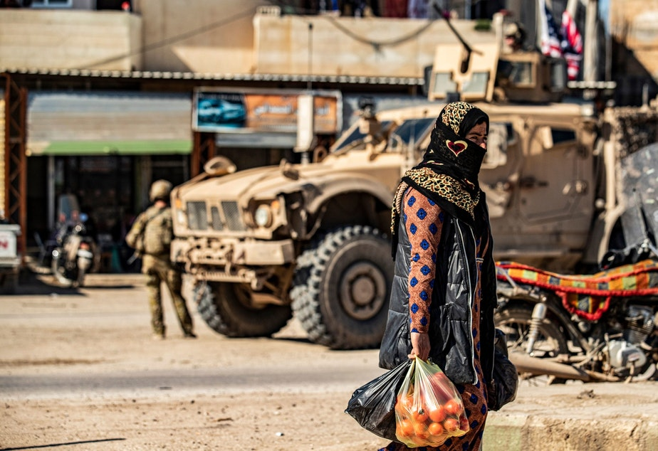 caption: A woman carrying produce walks past a US military armoured vehicle in the town of Tal Tamr along the M4 highway in the northeastern Syrian Hasakeh province, near the border with Turkey, on March 3, 2020. (DELIL SOULEIMAN/AFP via Getty Images)