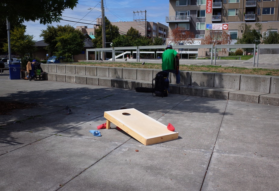 "caption: A corn hole game installed by the city of Seattle at Ballard Commons park. It is maintained by a ""concierge"" whose job is to build a comfortable atmosphere in the park."