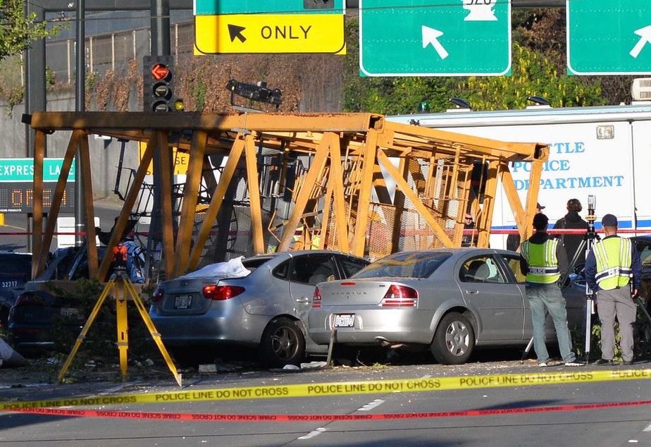 caption: Part of a crane that fell from a nearby building lies atop cars on Mercer Street on Saturday, April 27, 2019.