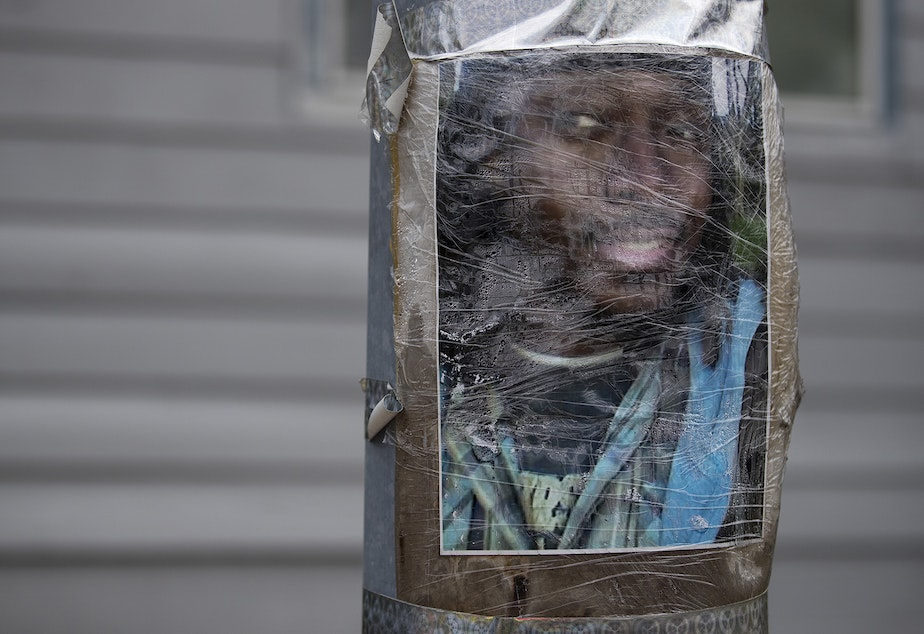 caption: An image of Manuel Ellis is taped to a utility pole on Thursday, June 4, 2020, near the intersection of Ainsworth Avenue South and 96th Street South in Tacoma. Ellis was killed by police on March 3rd.