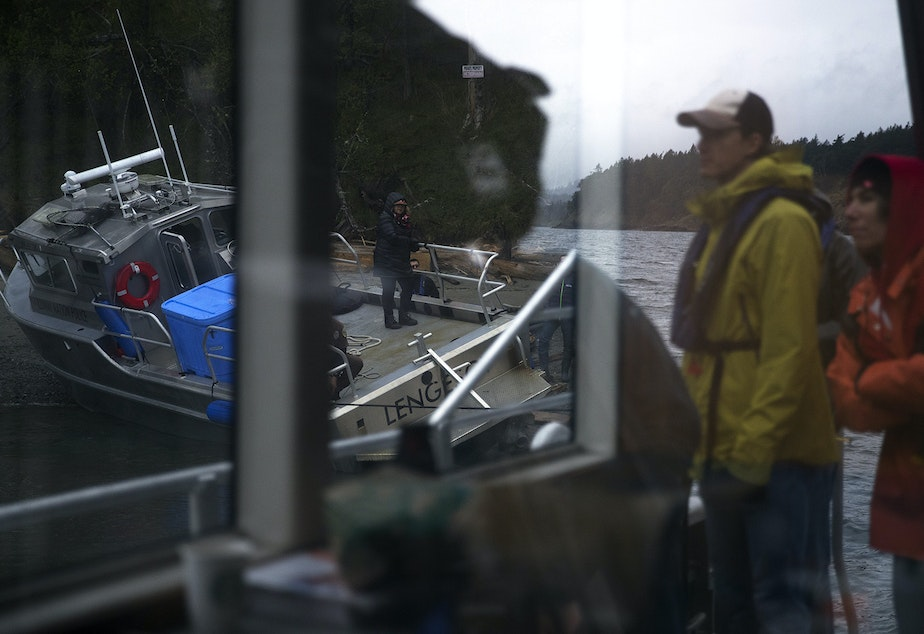 Jake Bullinger and Julie Trimingham, right, look on as attempts are made to free the Lummi Nation police boat after it was briefly grounded on Wednesday, April 10, 2019, on Henry Island.